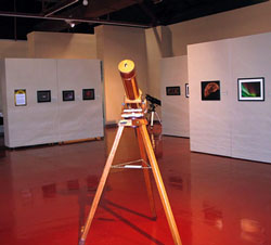 A Member Telescope stands before member astrophotos at the Las Cruces Fine Arts Museum